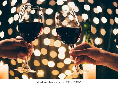 Cropped shot of two women clinking glasses with red wine in front of bokeh background