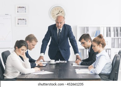 Cropped shot of an unhappy senior boss standing next to the table in the office