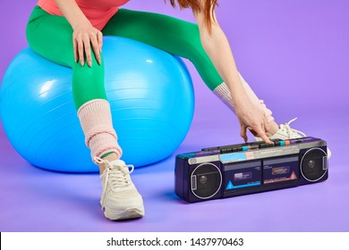 cropped shot of unrecognizable flexible fitness woman pressing the button on her retro portable cassette player to turn on music for cardio work out, sitting on blue fitness ball in green leggins and