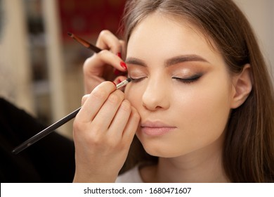 Cropped shot of unrecognizable makeup artist working at beauty salon, blending eyeshadow on eyelids of a female client