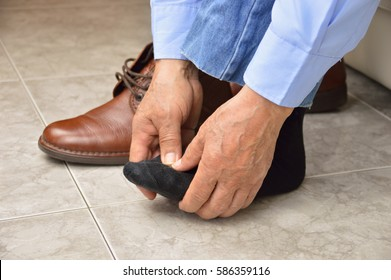 Cropped shot of an unrecognizable man suffering with foot cramp in the room