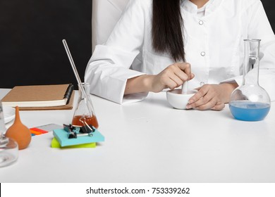 Cropped shot of unrecognizable woman pharmacist mixing ingredients, homogenizing mixture using mortar and pestle to make cream, working in lab, sitting at white desk with tools, flasks and notebook