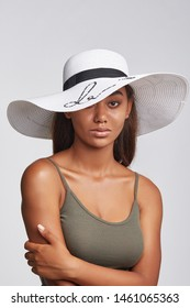 Cropped shot of upper body's part of dark-skinned brunette girl, wearing khaki-coloured tank top and white wide brim hat with black ribbon and sequins embroidery. She putting left hand on a shoulder.