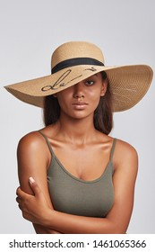 Cropped shot of upper body's part of dark-skinned brunette girl, wearing khaki-coloured tank top and sand-colored wide brim hat with black ribbon and sequins embroidery. She putting left hand on a sho