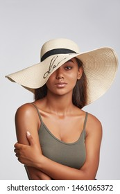 Cropped shot of upper body's part of dark-skinned brunette girl, wearing khaki-coloured tank top and beige wide brim hat with black ribbon and sequins embroidery. She putting left hand on a shoulder.