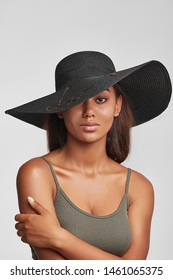 Cropped shot of upper body's part of dark-skinned brunette girl, wearing khaki-coloured tank top and black wide brim hat with black ribbon and sequins embroidery. She putting left hand on a shoulder.