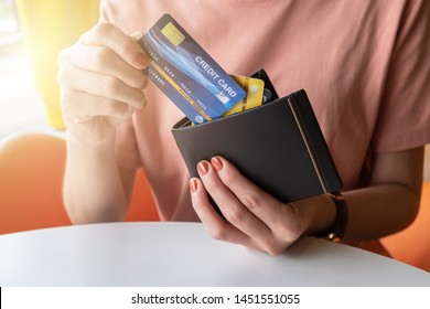 Cropped shot view of female hands picking credit cards from her wallet. Credit card lets cardholders borrow funds with which to pay for goods and services depend on the condition.