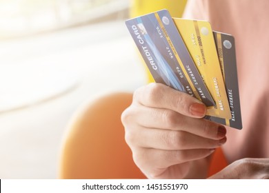 Cropped shot view of female hands holding her credit cards. Credit card lets cardholders borrow funds with which to pay for goods and services depend on the condition that cardholders pay back.