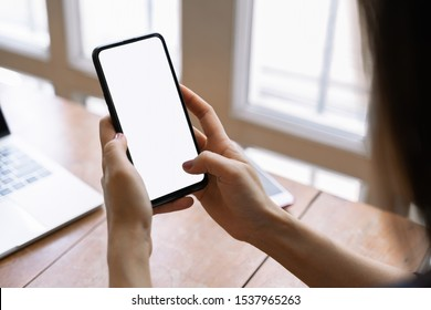 Cropped shot view of female hands holding smart phone with blank screen for your text message or information content.