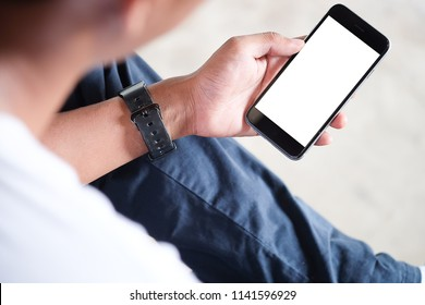 Cropped shot view of man hands holding smart phone with blank copy space screen for your text message or information content, female reading text message on cell telephone during in urban setting