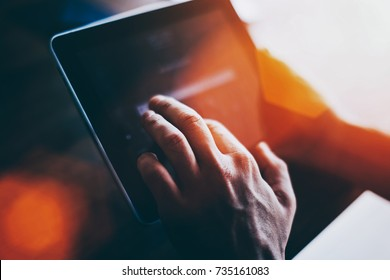 Cropped shot view of a man's hand touching digital tablet screen with copy space for your text message or advertising content, successful male using touch pad for remote work during recreation time
