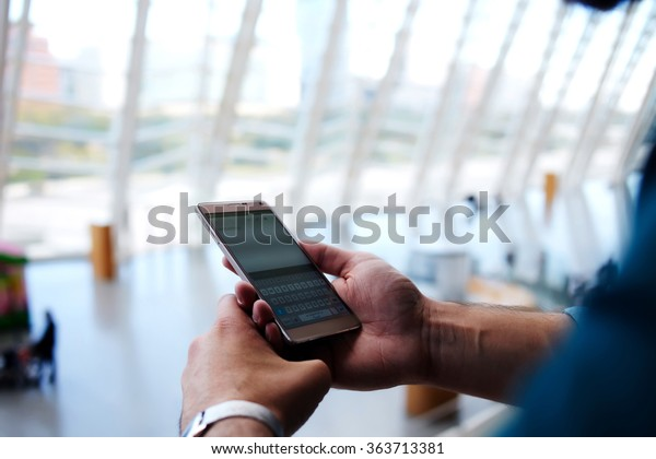 Cropped shot view of man's hands orders electronic ticket via mobile phone application during summer trip, young male reading text message on cell telephone while standing in waiting hall of airport