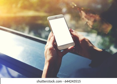 Cropped shot view of a woman's hands holding mobile phone with empty copy space screen for your text message or advertising content, young female person chatting on cell telephone during work break