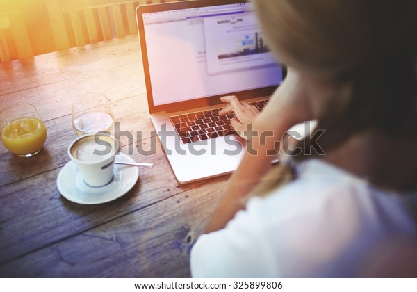 Cropped shot view of a women's hands keyboarding on laptop, young female person working on net-book while sitting in coffee shop indoors, blonde female freelancer connecting to internet via computer