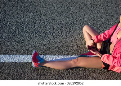 Cropped shot view of young female runner using mobile phone while sitting on a road with copy space background for your text or content, fit woman using cell telephone while resting after training