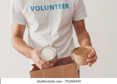 cropped shot of volunteer putting tin cans in paper bag
