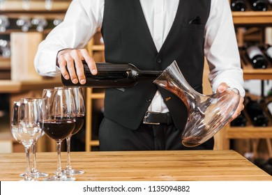 cropped shot of wine steward pouring wine into decanter at wine store