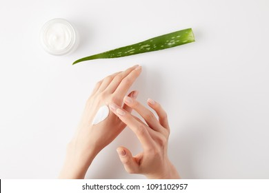 cropped shot of woman applying organic cream on hands, aloe vera leaf and cream container on white surface
