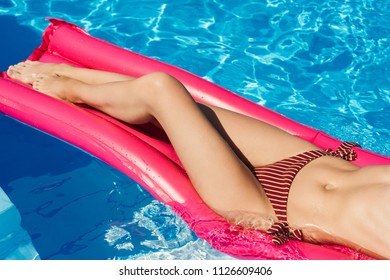 cropped shot of woman in bikini floating on inflatable mattress at swimming pool