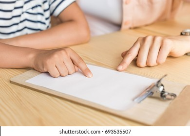 cropped shot of woman and boy pointing at blank paper on clipboard