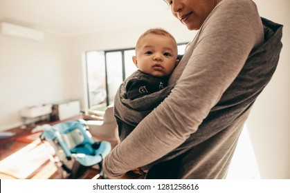 Cropped shot of a woman carrying her baby in a baby sling carrier at home. Close up of a baby sitting comfortably in a sling carrier worn by his mother.