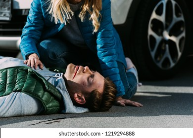 cropped shot of woman checking heartbeat of victim after traffic collision