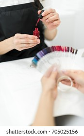 cropped shot of woman choosing nail polish color