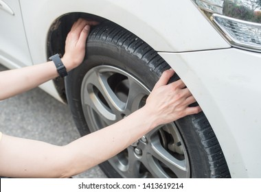 Cropped shot of woman hands touching and checking her car tyre. She worrying about somethings wrong with her wheel.
