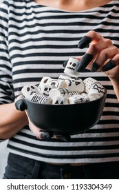 cropped shot of woman holding bowl of marshmallows with skull faces, halloween concept