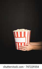 cropped shot of woman holding bucket of popcorn isolated on black