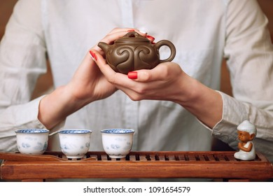 Cropped shot of woman holding clay teapot in front of the camera.