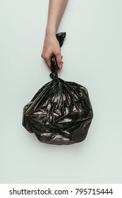 cropped shot of woman holding garbage bag in hand isolated on grey