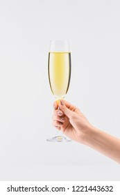 cropped shot of woman holding glass of champagne in hand isolated on white