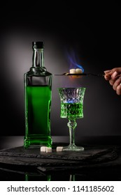 cropped shot of woman holding spoon with sugar cubes over burning absinthe in glass on dark background
