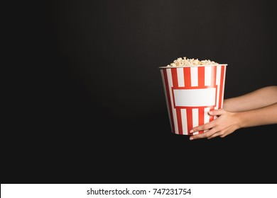 cropped shot of woman holding striped bucket of popcorn isolated on black
