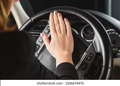 cropped shot of woman honking horn while driving car