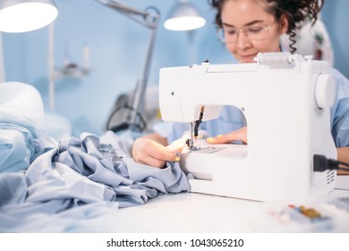 cropped shot of woman learning to sew on sewing machine in design studio. attending lessons of sewing. hobby. free time