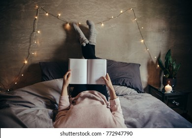 Cropped shot of woman lying on bed and reading book. Female hands holding a book while lying on bed.