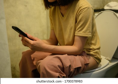 Cropped shot of woman playing her phone while sitting on toilet bowl. Conceptual of woman privacy time in toilet.