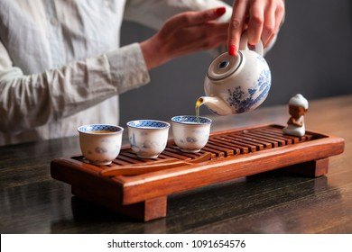 Cropped shot of woman pouring tea in traditional chinese teaware.