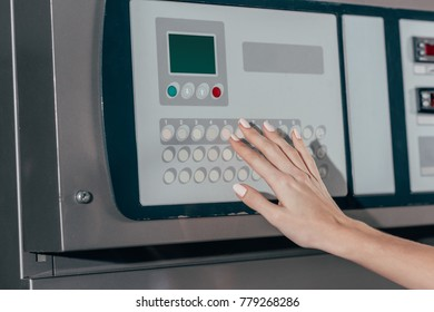 cropped shot of woman pressing buttons on industrial washing machine