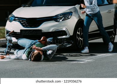 cropped shot of woman running to injured cyclist at traffic accident