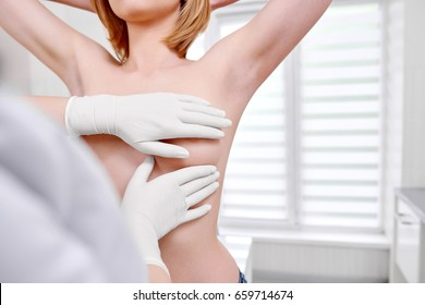 Cropped shot of a woman standing topless getting her breast examined during medical appointment at the hospital copyspace cancer awareness prevention examination checkup medicine health.