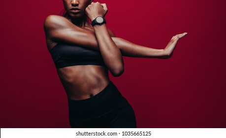 Cropped shot of woman stretching her arms. Female doing warmup stretching workout on red background.