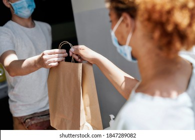 Cropped shot of woman wearing mask taking paper bag with her order from hands of shop assistant while collecting her purchase from the pickup point. Selective focus on hands and bag. Horizontal shot