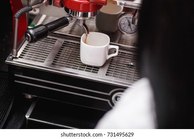 Cropped shot of a woman's barista with coffee with a coffee maker