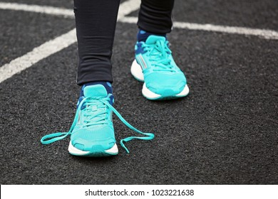Cropped shot of a woman's legs in running shoes with loose shoelaces.