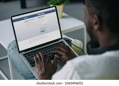 cropped shot of young african american man using laptop with facebook website on screen