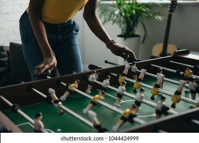 cropped shot of young african american woman playing foosball
