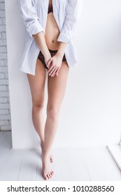 cropped shot of young barefoot woman in lingerie and shirt standing at home